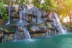 Vattenfallet i trädgård på det offentligt parkerar arkivfoton