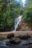 Vattenfallet i tropisk rainforest med vaggar Arkivbild