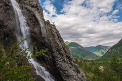 Vattenfallet i vaggar på bakgrunden av berg Arkivfoto