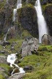 Vattenfallet och basaltiskt vaggar. Island. Seydisfjordur. Arkivfoton