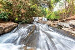Vattenfallet och gräsplan strömmar i skogen Thailand Royaltyfri Fotografi