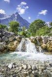 Vattenfallet och vaggar i de österrikiska fjällängarna Fotografering för Bildbyråer