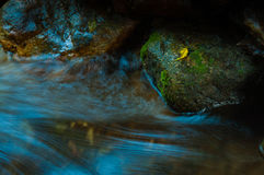 Vattenfallet och vaggar med bladet i mörk nyckel- och lång exponering för bottenläge Fotografering för Bildbyråer