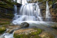 Vattenfallet på en bergflod med grön mossa täckte stenblock royaltyfri fotografi
