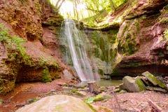Vattenfallet på röda stenar, vaggar i träna Fotografering för Bildbyråer