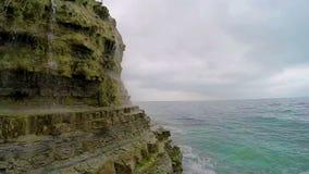 Vattenfallet som faller från en klippa, och havet surfar arkivfilmer