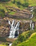 vattenfallet stenar den gr?na mossaregnskogen royaltyfria foton
