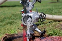 Vattenflöde som är kommande ut från en brandpost Arkivfoton