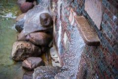Vattenflöden från springbrunnen Vatten häller från stenen royaltyfri foto