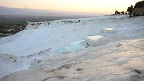 Vattenflöden in i den Pamukkale travertinen terrasserar på solnedgången arkivfilmer