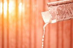 Vattenflöden till och med avrinningröret smältande snow kom fjädern arkivbild