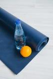 Vattenflaska, apelsin och matt yoga Arkivfoto