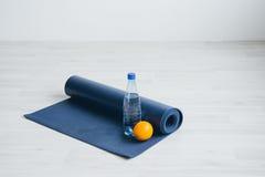 Vattenflaska, apelsin och matt yoga Royaltyfri Bild