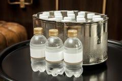 Vattenflaska med den tomma etiketten på ett utsmyckat rum royaltyfria foton