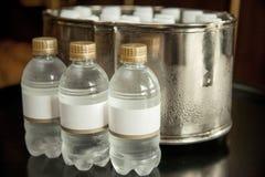 Vattenflaska med den tomma etiketten på ett utsmyckat rum royaltyfria bilder