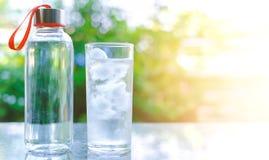 Vattenflaska och ett exponeringsglas av is på suddig naturlig grön backgro royaltyfria bilder