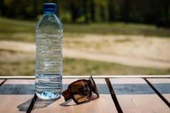 Vattenflaska och solglasögon på tabellen på en solig dag fritid arkivfoton