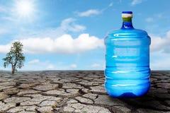 Vattenflaska på det spruckna landet Arkivfoto