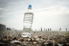Vattenflaska på skal på stranden Arkivfoton