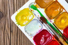 Vattenfärger, målarfärg-ask och en borste Arkivbild