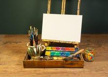Vattenfärger och borstar för palett för konstnärstudiostaffli med tom vit kanfas Royaltyfri Fotografi