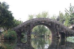 Vattenhjul bågebro, gataljus, träd, stenar, sjö, landskap royaltyfri bild