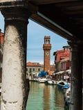 Vattenkanal med fartyg och San Giacomo Bell Tower i Murano Isla Arkivfoton