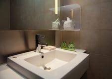 Vattenklapp och keramisk vit vask i en modern WC med bruna tegelplattor Arkivfoton