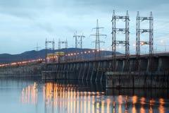 Vattenkraft posterar på floden på aftonen Arkivbild