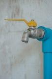 Vattenkran med waterfrop och gammal väggbakgrund Arkivfoto