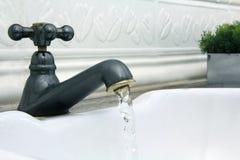 Vattenkran som ut kommer vatten i den vita vasken royaltyfri fotografi