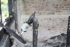Vattenkranen och röret i hem- brand specificerar brandkatastrof arkivbilder