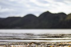 Vattenkrusningar pÃ¥ kust med berg i avstÃ¥nd Försiktiga sjöstrandvÃ¥gor fotografering för bildbyråer