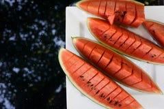 Vattenmelon för lägenhet för bästa sikt lekmanna- skivad röd på plattan på den svarta glass tabellen med träd i reflexion Sommarm Arkivfoto