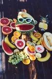 Vattenmelon i rolig solglasögon med leende Stilleben för nya frukter på trätabellen Vegetarisk mat för detox bantar och fotografering för bildbyråer