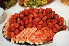 Vattenmelon med jordgubbar på färgbakgrund Arkivfoto