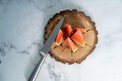 Vattenmelon som klipps in i förnyande delar på träplattan på den vita marmortabellen arkivfoton