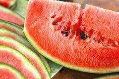 Vattenmelonfrukt som skivas in i stycken på trägolvet. Royaltyfri Foto