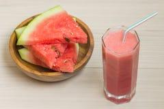 Vattenmelonfruktsaft i ett glass exponeringsglas med ett sugrör på en ljus träbakgrund, en coctail, en platta med skivor av moget Fotografering för Bildbyråer