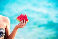 Vattenmelonskiva i kvinnahanden över havet - POV Sommarstrandbegrepp Tropisk frukt bantar royaltyfri foto