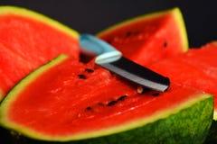 Vattenmelonskiva med kniven Arkivfoto