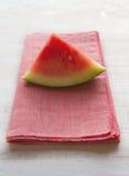 Vattenmelonskiva på rosa servettplacemat Arkivbild