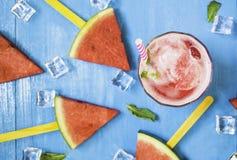 Vattenmelonskivor och mintkaramell med smoothies i klara exponeringsglas och is på ljus blå träbakgrund, organiskt frukticke-gift arkivbild