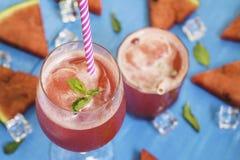 Vattenmelonskivor och mintkaramell med smoothies i klara exponeringsglas på ljus blå träbakgrund, organiskt frukticke-gift för be royaltyfri fotografi