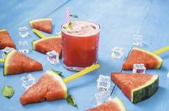 Vattenmelonskivor och mintkaramell med smoothies i klara exponeringsglas p? ljus bl? tr?bakgrund, organiskt frukticke-gift f?r be arkivfoton