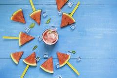 Vattenmelonskivor och mintkaramell med smoothies i klara exponeringsglas och is p? ljus bl? tr?bakgrund, organiskt frukticke-gift arkivbilder