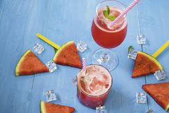Vattenmelonskivor och mintkaramell med smoothies i klara exponeringsglas p? ljus bl? tr?bakgrund, organiskt frukticke-gift f?r be royaltyfri fotografi