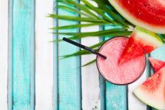 Vattenmelonsmoothie, ny fruktsaft på färgrik träbakgrund med palmblad Top beskådar kopiera avstånd royaltyfria bilder
