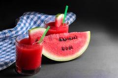 Vattenmelonsmoothies med en skiva av den mogna vattenmelon på en svart bakgrund Royaltyfri Fotografi
