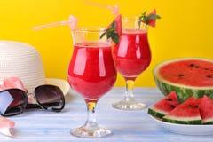 Vattenmelonsmoothies med mogen vattenmelon- och sommartillbehör på en ljus gul bakgrund Royaltyfria Bilder